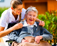 old woman in a wheelchair with her caregiver